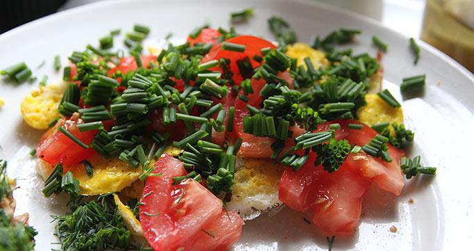 Masser af frisk purløg på spejlæg og tomat. Tomaten er købt.