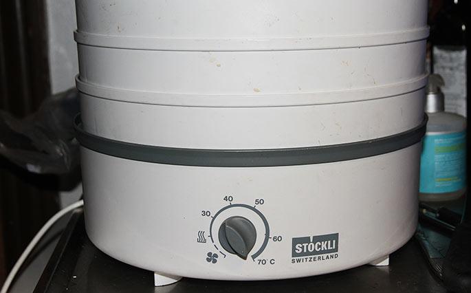 Bakkerne sættes oven på selve tørremaskinen. Øverst er der et lag med hul i m