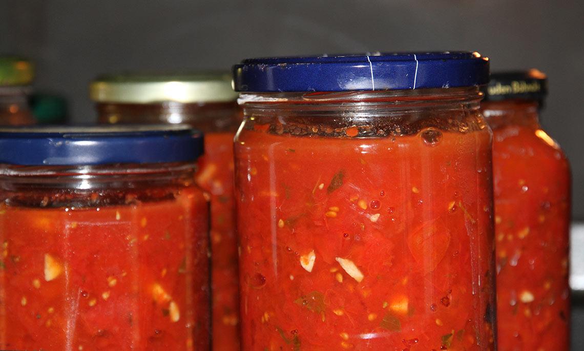 Den kogte tomatsauce er nu i glas med undertryk.