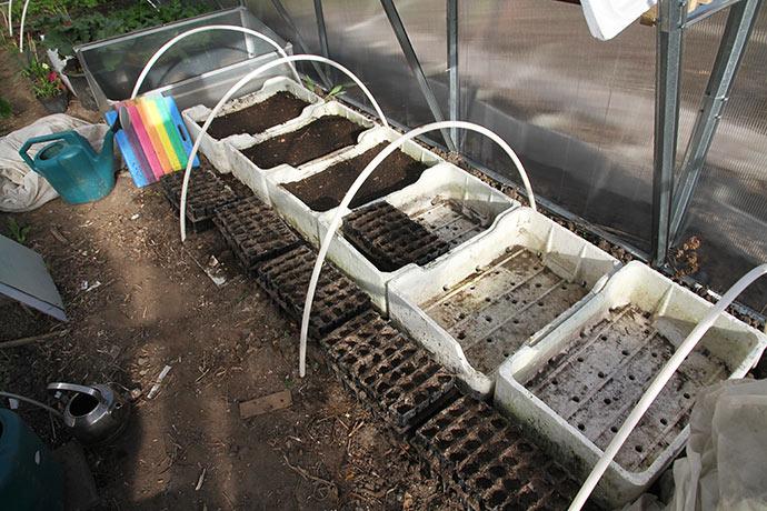 Såkasser med jord til porrer og forårsløg. rootrainerne skal efter såning sættes ned i de andre kasser.
