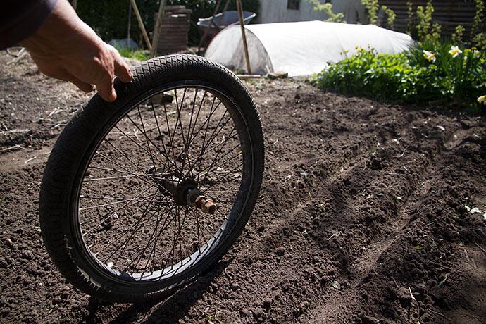 Cykelhjulet kan trilles hen over bunden i sårillen og jævne jorden.