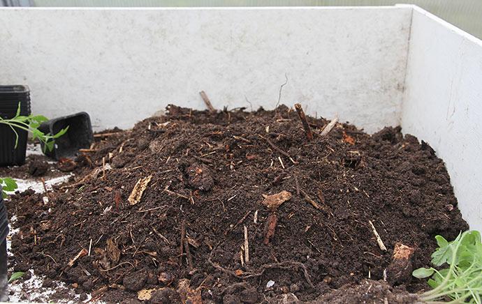 En spand kompost er hældt ud til sortering.