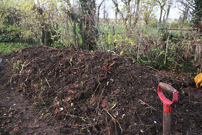 Nederst er det nye friske kompostmateriale lagt - ovenpå det delvis omsatte.