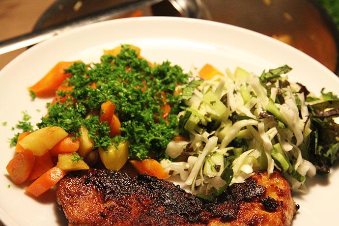 Sauterede rodfrugter med persilledrys, salat og en skinkeschnitzel vendt i paprika.