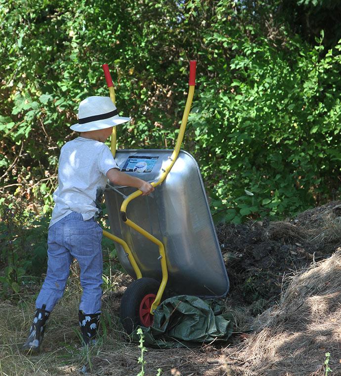 Endnu en trillebør visne græstørv til kompost.